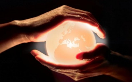 mundo iluminado entre dos manos